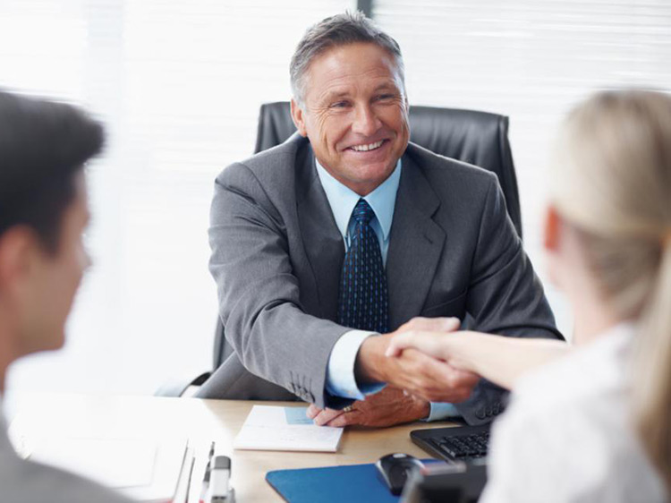 Man shaking a woman's hand at a business meeting